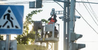 Рабочие устанавливают камеру фиксации нарушений ПДД в Бишкеке в рамках проекта Безопасный город