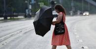 Девушка переходит улицу по пешеходному переходу в Москве во время дождя.