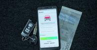Ключ от автомашины, деньги и открытое мобильное приложение Штраф Инфо KG