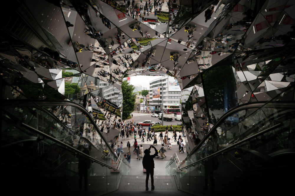 Турист фотографируется у входа в торговый центр, украшенный зеркалами, в Токио