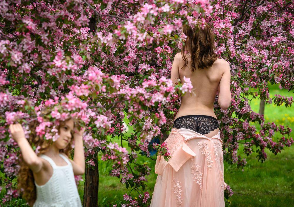 Девушка позирует во время фотосессии в вишневом саду в московском музее-заповеднике Коломенское