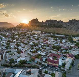 Вид на гору Сулайман-Тоо в центре города Ош во время заката