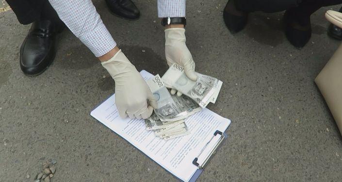 Сотрудница Центра образования Октябрьского района Бишкека во время задержания с поличным при получении взятки в 15 тысяч сомов