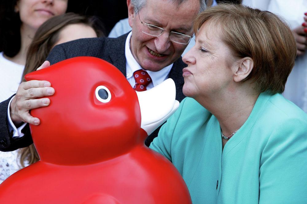Канцлер Германии Ангела Меркель с игрушечной уткой во время посещения биотехнологической компании Centogene в Ростоке. Германия.