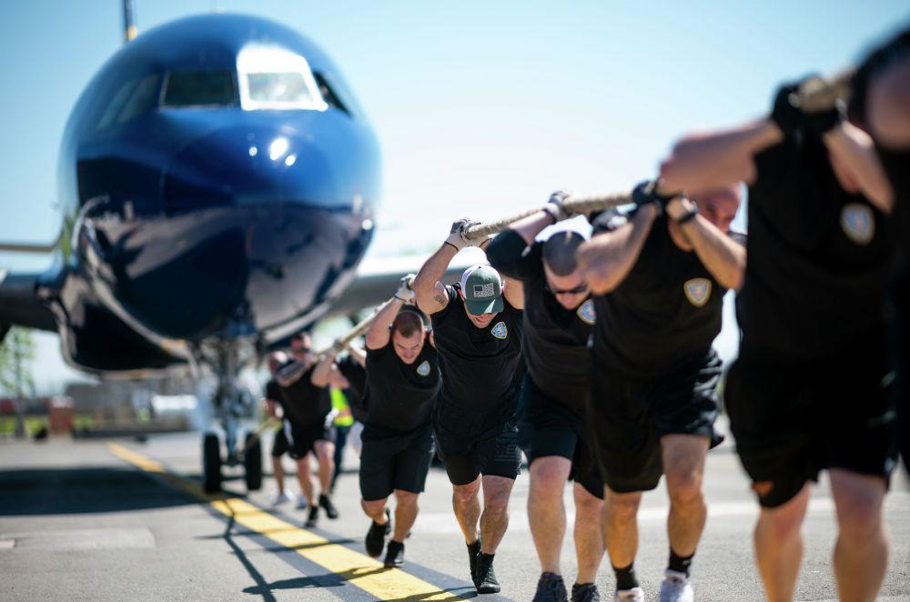 Мужчины тянут самолет JetBlue A320 во время ежегодных соревнований Plane Pull в международном аэропорту Джона Кеннеди в Нью-Йорке.