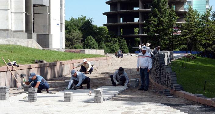 Рабочие во время закладки плит у Кыргызской национальной филармонии им. Т. Сатылганова.