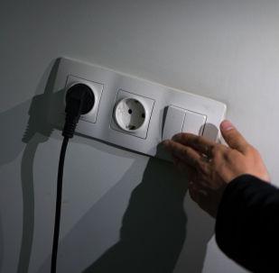 Парень включает освещение в комнате. Архивное фото