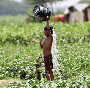 Мальчик поливает себя водой в жаркий день в Нью-Дели (Индия)
