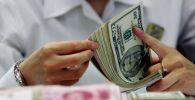 Сотрудница банка пересчитывает доллары США. Архивное фото
