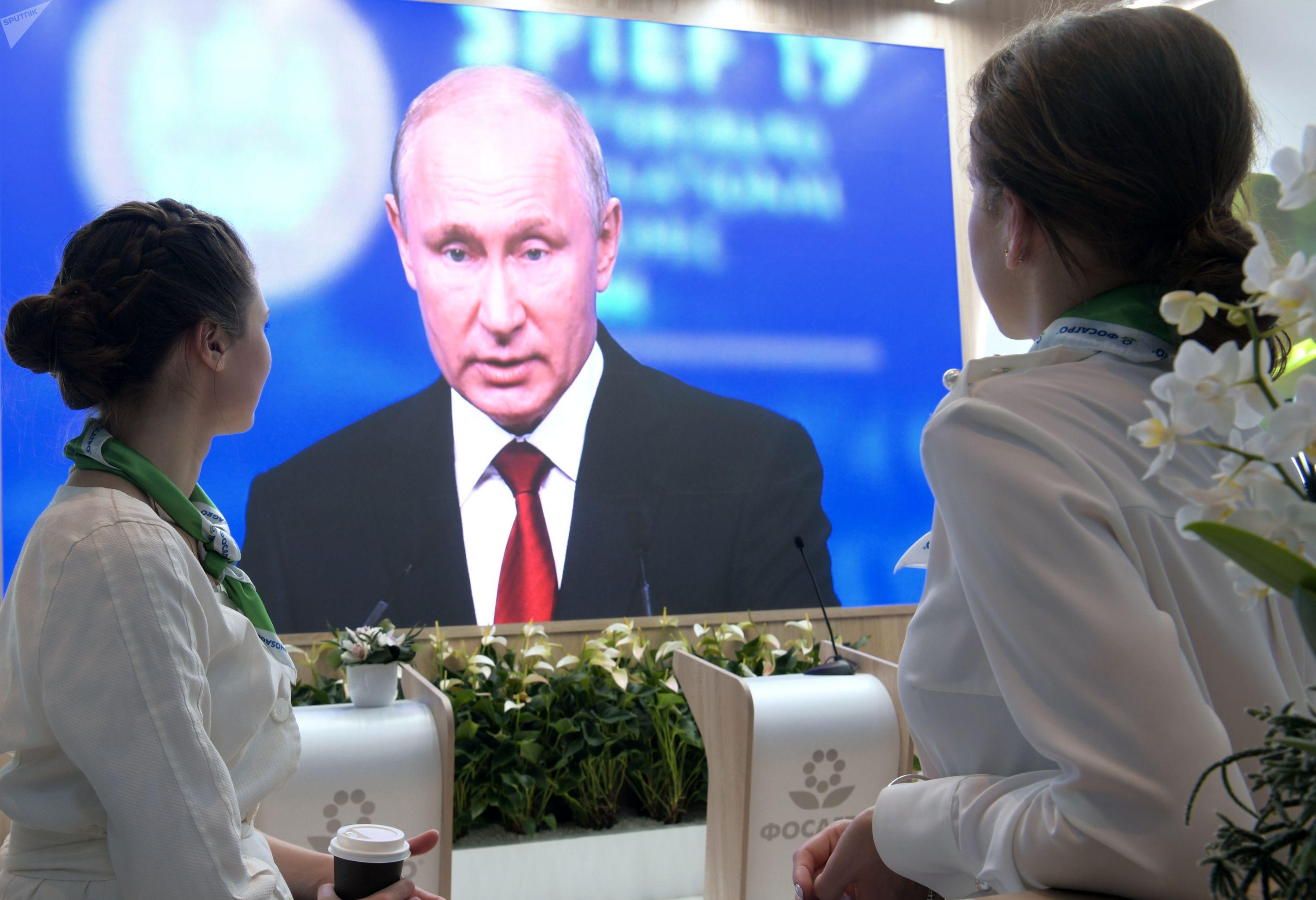 Участницы Петербургского международного экономического форума 2019 (ПМЭФ-2019) на стенде компании Фосагро смотрят трансляцию выступления президента РФ Владимира Путина.