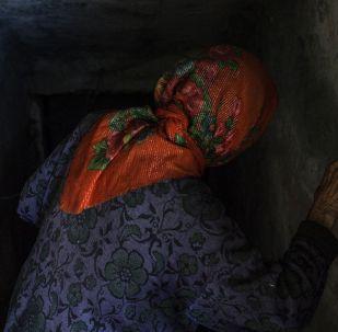 Пожилая женщина спускается в подвал. Архивное фото