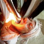 Член иракских мусульманских суфийских дервишей кладет в рот горящий факел, принимая участие в ритуале во время священного для мусульман месяца Рамадан в Эрбиле. Ирак, 19 мая 2019 года.