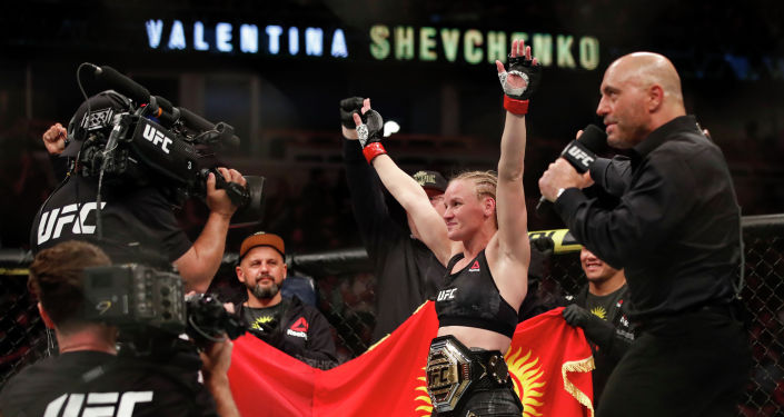 Валентина Шевченко празднует победу над Джессикой Ай во время поединка за титул в полусреднем весе среди женщин в UFC 238. Чикаго 8 июня 2019 года