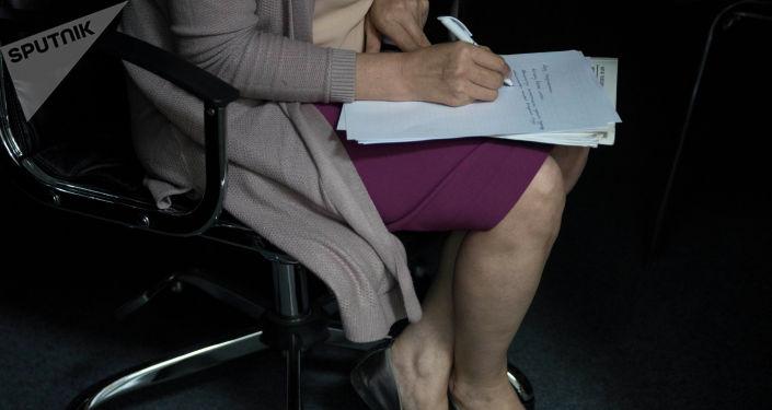 Женщина пишет на листе бумаги сидя в кресле