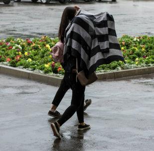 Девушки прикрываются от дождя. Архивное фото