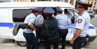 Полицейские задерживают сторонника оппозиции во время акции протеста против результатов президентских выборов в Алматы. Архивное фото