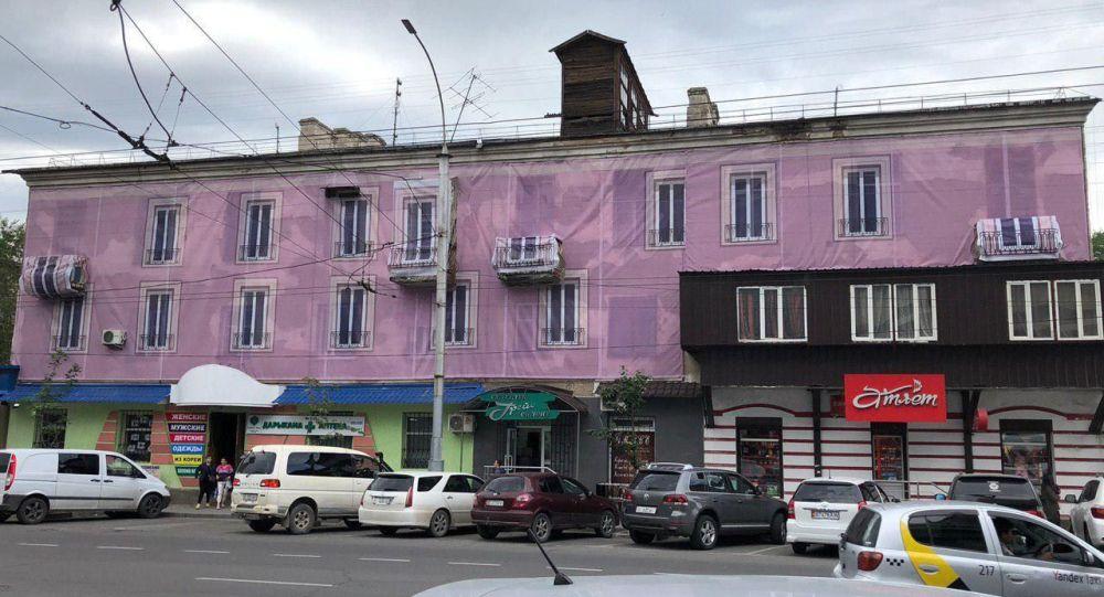 Жилой дом напротив торгового центра Бишкек Парк в Бишкеке, фасад которого прикрыли большим баннером розового цвета