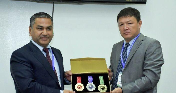 Директор ГАМФКиС Канат Аманкулов вручает подарок на заседании молодежного совета ШОС в Бишкеке