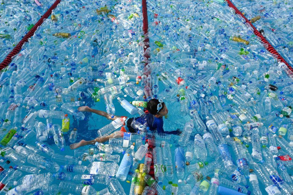 Ребенок плавает в бассейне, наполненном пластиковыми бутылками. Кампания в Бангкоке (Таиланд) приурочена к Всемирному дню океанов.