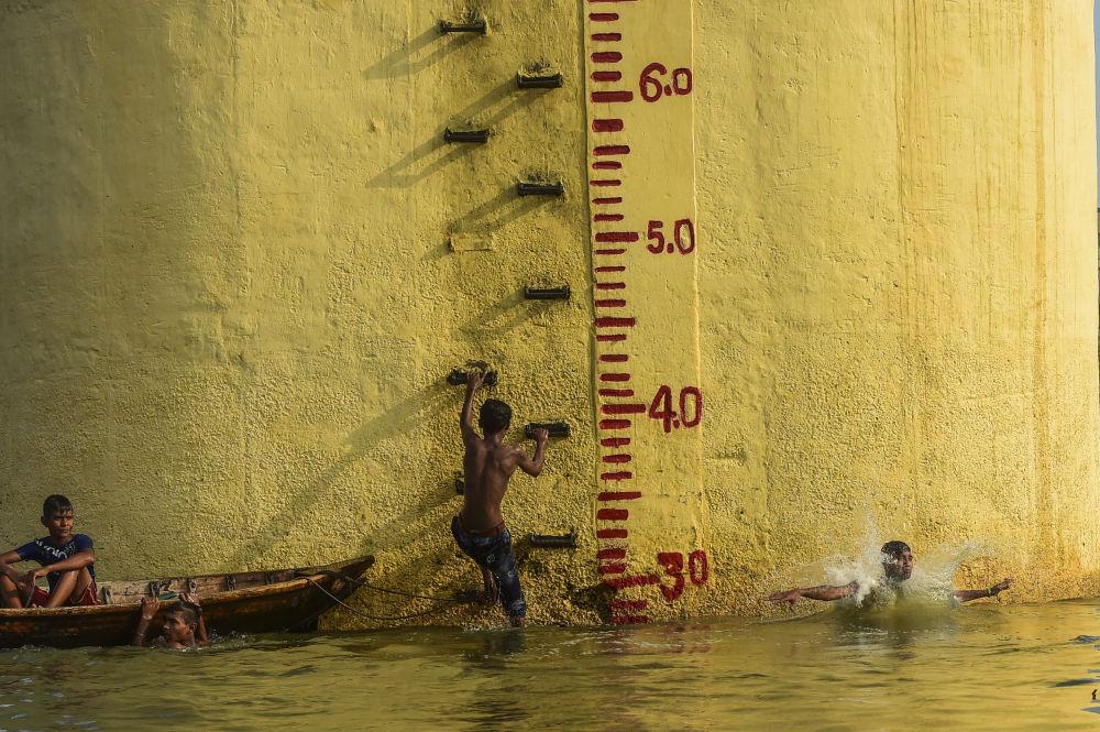 Молодые люди купаются в реке Буриганга в Дакке (Бангладеш)