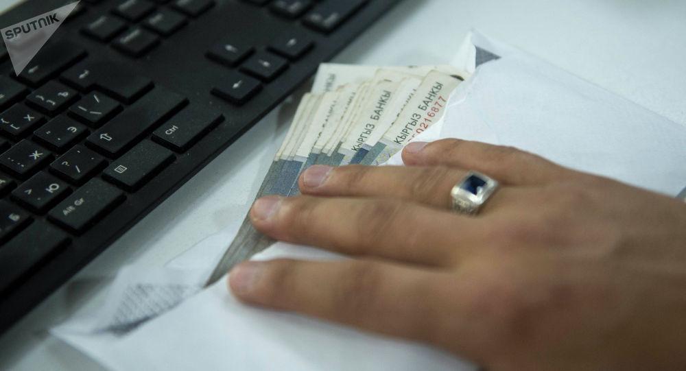 Мужчина держит конверт с деньгами на столе