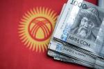 Одна тысячные сомовые купюры на фоне флага Кыргызской Республики. Архивное фото