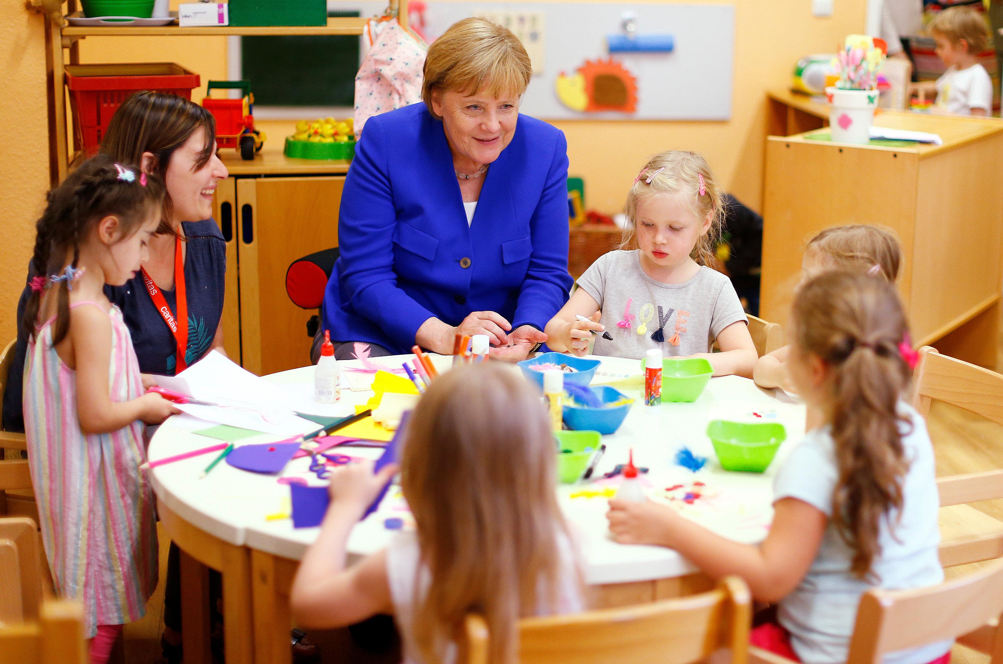 Канцлер Ангела Меркель сидит с детьми в детском саду Ассоциации Каритас в Кельне. Германия, 18 июля 2018 года