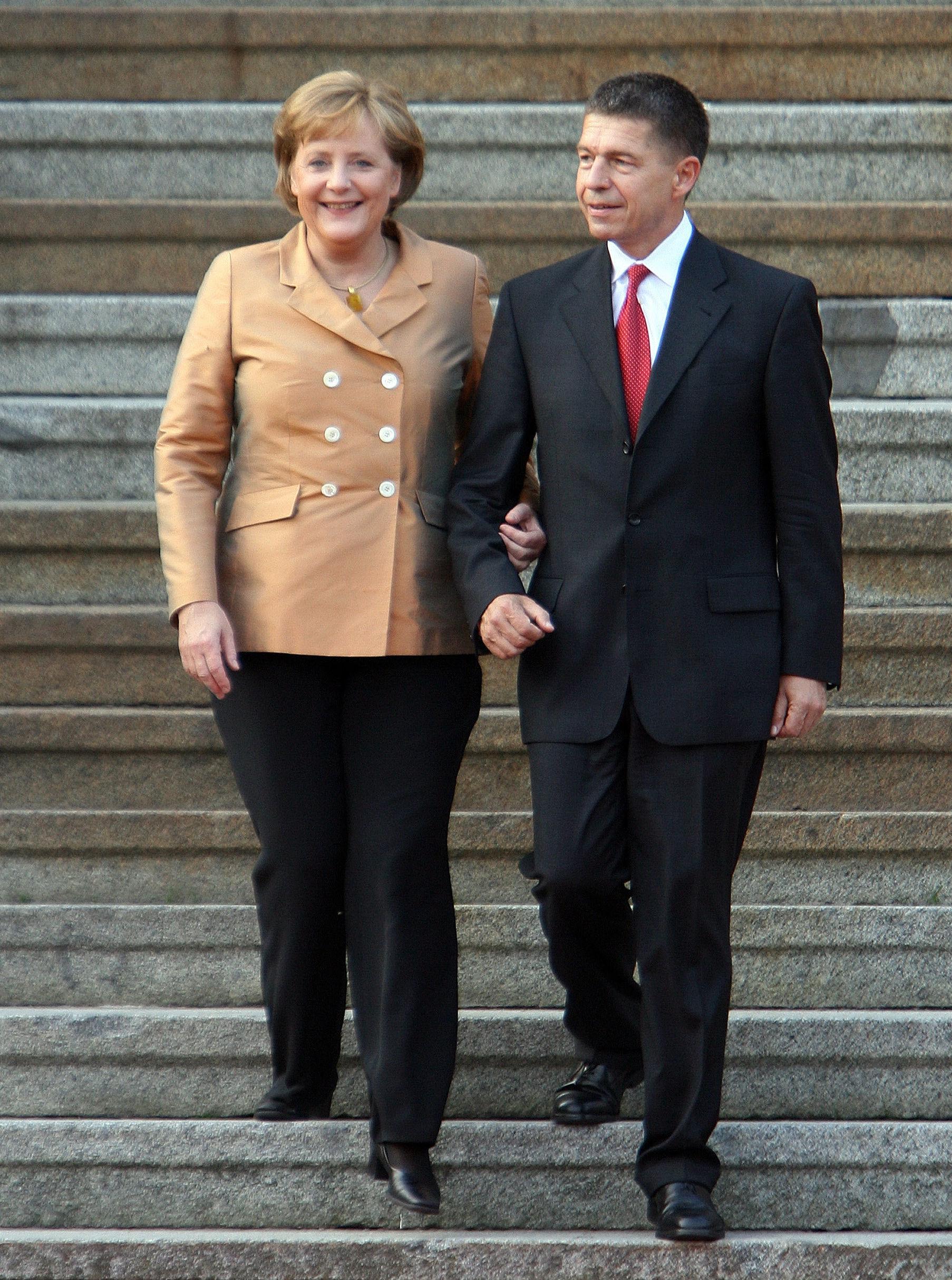 Канцлер Германии Ангела Меркель и ее муж Йоахим Зауэр спускаются по лестнице, чтобы приветствовать лидеров саммита G8 на неофициальном банкете, организованной Меркель во время встречи на высшем уровне G8 в Хоэне Лукове. 06 июня 2007 года