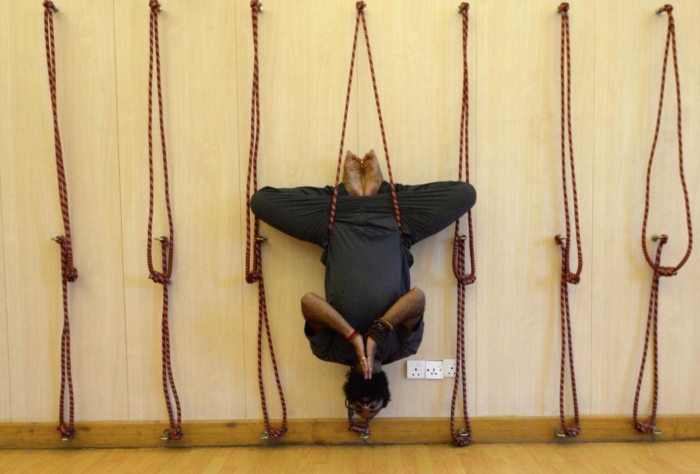 Преподаватель непальской йоги Рамеш Сапкота демонстрирует воздушную йогу в своей студии перед Международным днем йоги в Катманду. 20 июня 2019 года.