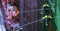 Американский канатоходец Ник Валленда и его сестра Лиджана проходят по канату, натянутому между небоскребами на высоте 25-го этажа над площадью Таймс-сквер в Нью-Йорке. 23 июня 2019 года