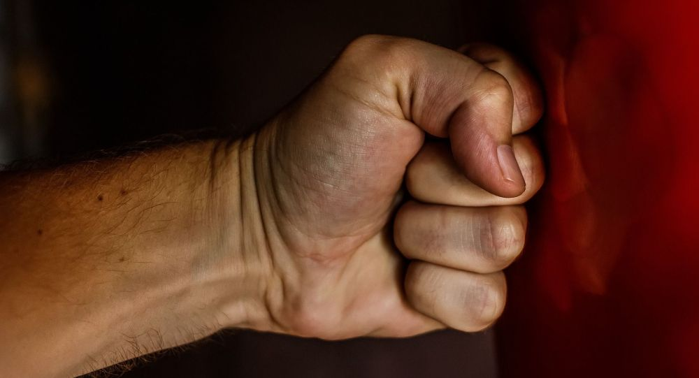 Мужчина бьет кулаком по груше