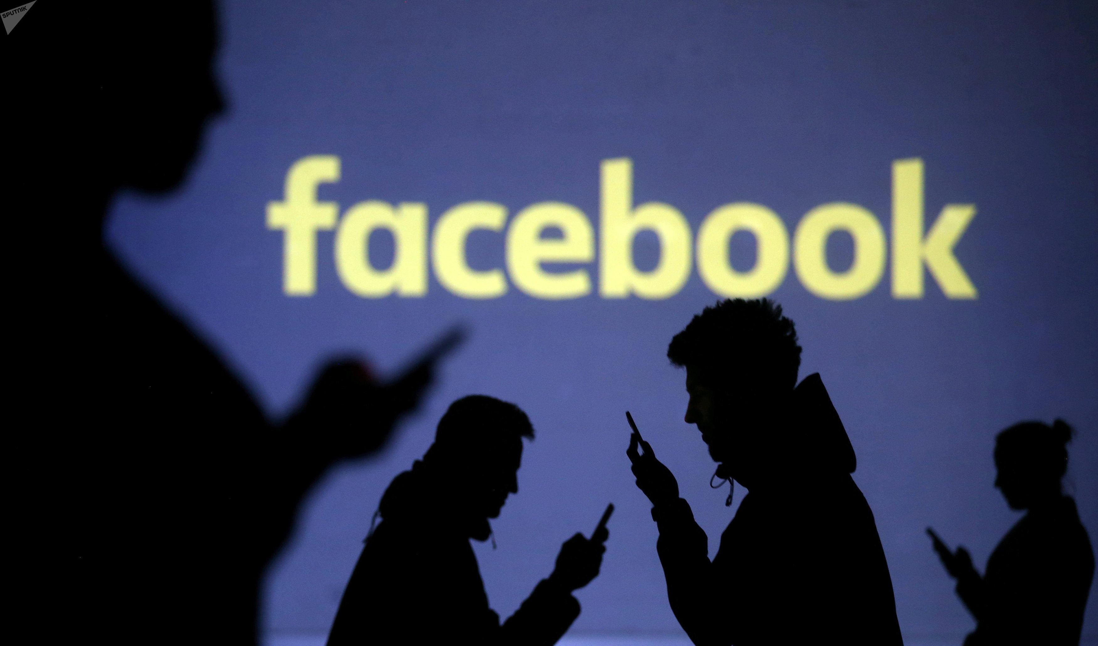 Силуэты мобильных пользователей видны рядом с экранной проекцией логотипа Facebook на этой иллюстрации. 28 марта 2018 года