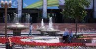 Горожане у фонтанов на площади Ала-Тоо в Бишкеке в жаркий летний день