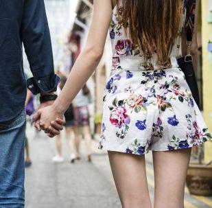 Парень и девушка держатся за руки. Архивное фото