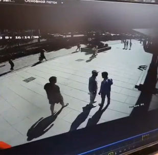 На кадрах видно, как мужчины разговаривают, после этого молодой человек тянет нигерийца в сторону за рукав, а тот отмахивается.
