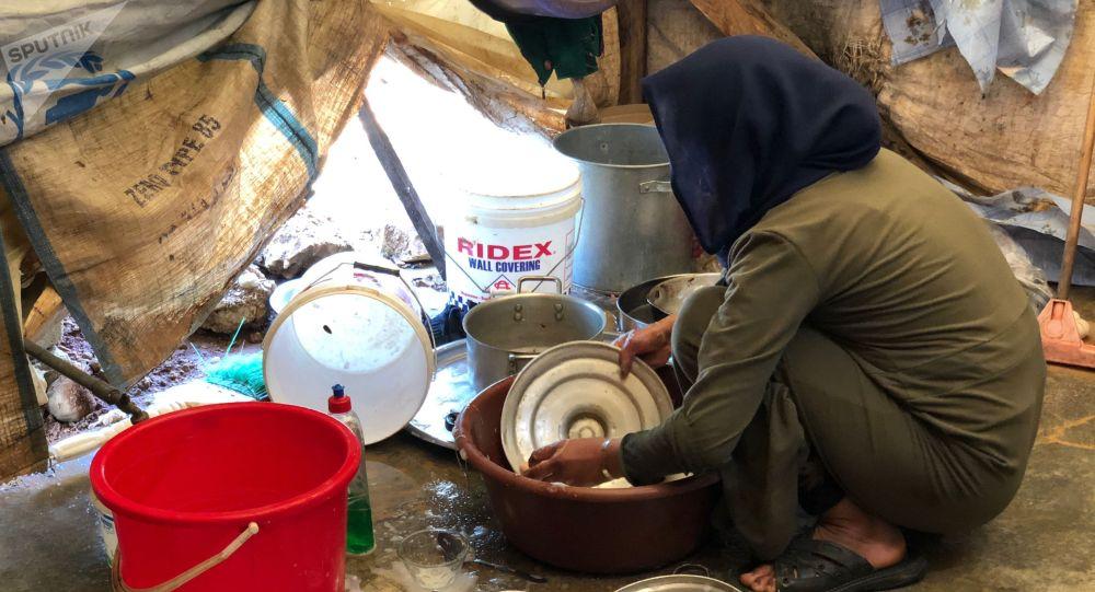 Сирийская женщина может посуду в лагере. Архивное фото