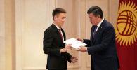 Президент Кыргызской Республики Сооронбай Жээнбеков и набравший самый высокий балл на ОРТ (238) Элдияр Чормонов из Джалал-Абада на церемонии вручения золотых сертификатов выпускникам 2019 года.