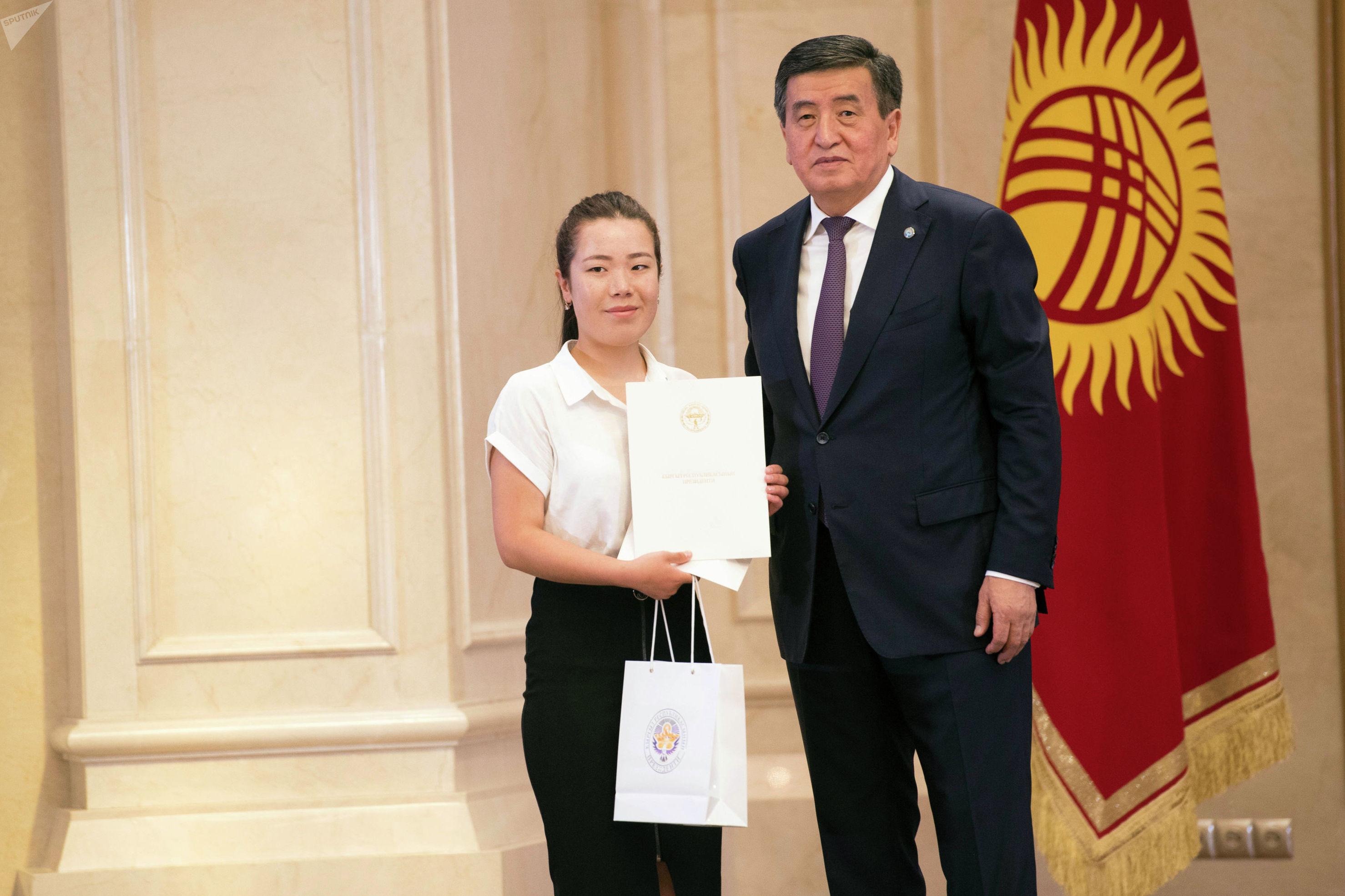 Президент Кыргызской Республики Сооронбай Жээнбеков и набравший высокий балл на ОРТ (231) Аида Борулукова из Лейлекского района Баткенской области на церемонии вручения золотых сертификатов выпускникам 2019 года