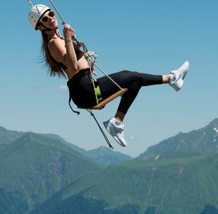 Девушка катается на тарзанке на горнолыжном курорте Роза Хутор в Сочи.