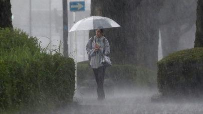 Пешеход идет сквозь сильный дождь в Кирисиме, префектура Кагосима на юго-западе Японии. 3 июля 2019 года
