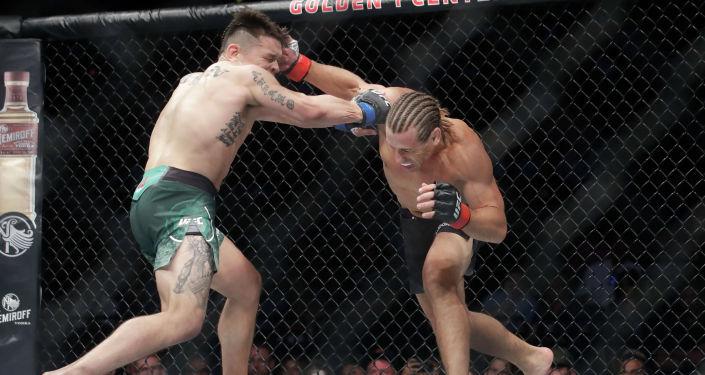 Урия Фабер (справа) наносит удар Рику Саймону во время боя из смешанных боевых искусств в легком весе на UFC Fight Night в Сакраменто. Калифорния, 13 июля 2019 года.