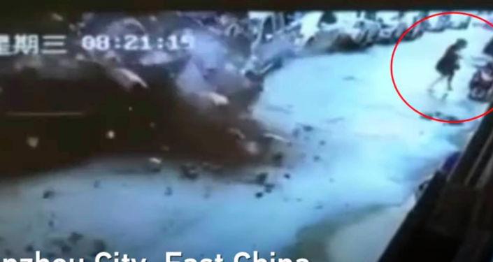 На одной из улиц китайского города Гуанчжоу внезапно рухнула огромная стена, и чуть не погребла заживо проходившую мимо женщину.