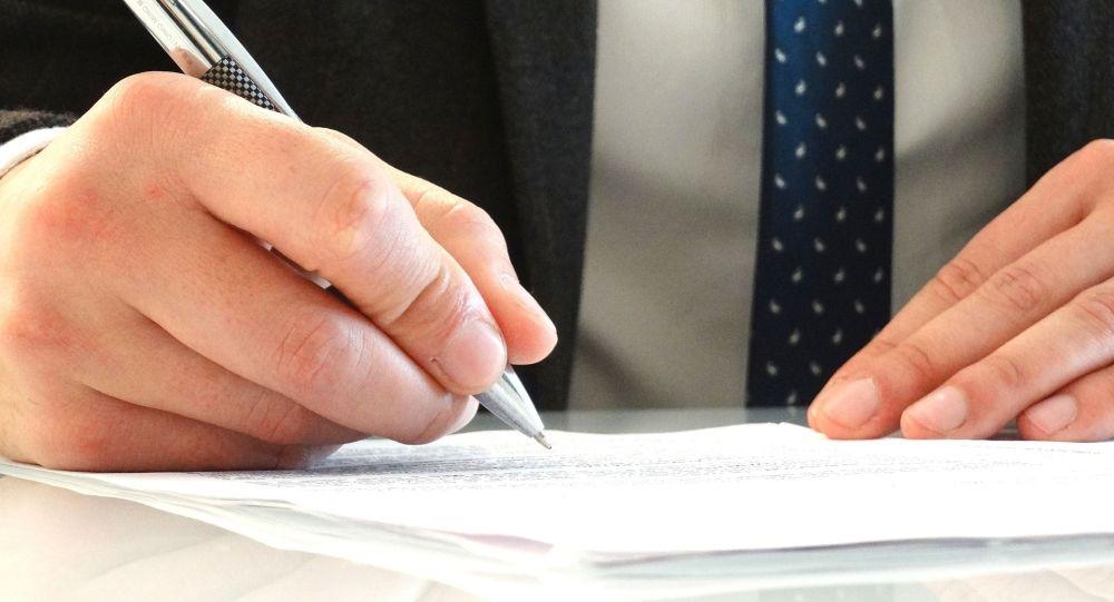 Мужчина пишет на бумаге ручкой. Архивное фото
