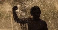 Мальчик купается в фонтане. Архивное фото