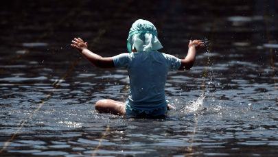 Мальчик играет у фонтана в жаркий день. Архивное фото