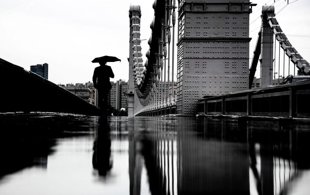 Прохожий на Крымском мосту во время дождя