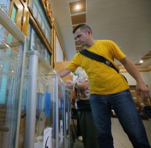 Украинанын Жогорку Радасына болгон шайлоодо добуш берип жаткан адам