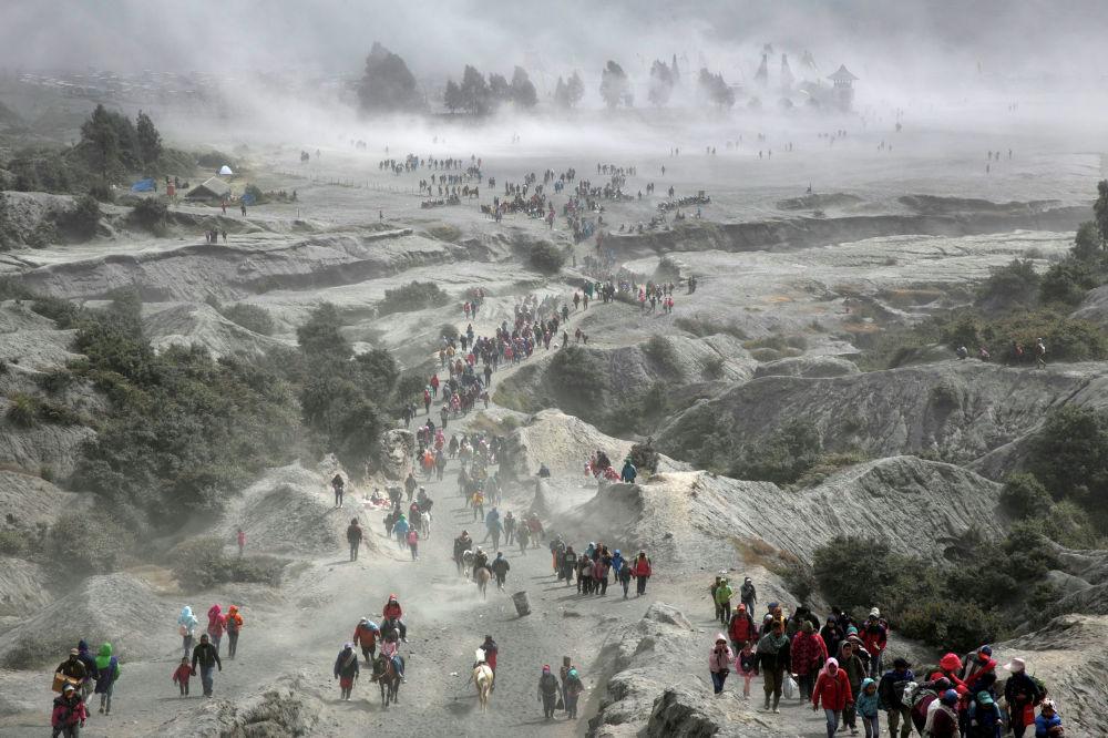 Тенгеры и туристы у вулкана Бромо во время фестиваля Yadnya Kasada в Индонезии.