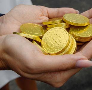 Девушка держит в ладонях символические монеты биткоина. Архивное фото