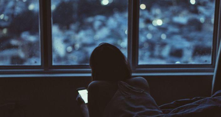 Девушка за смартфоном лежит в кровати